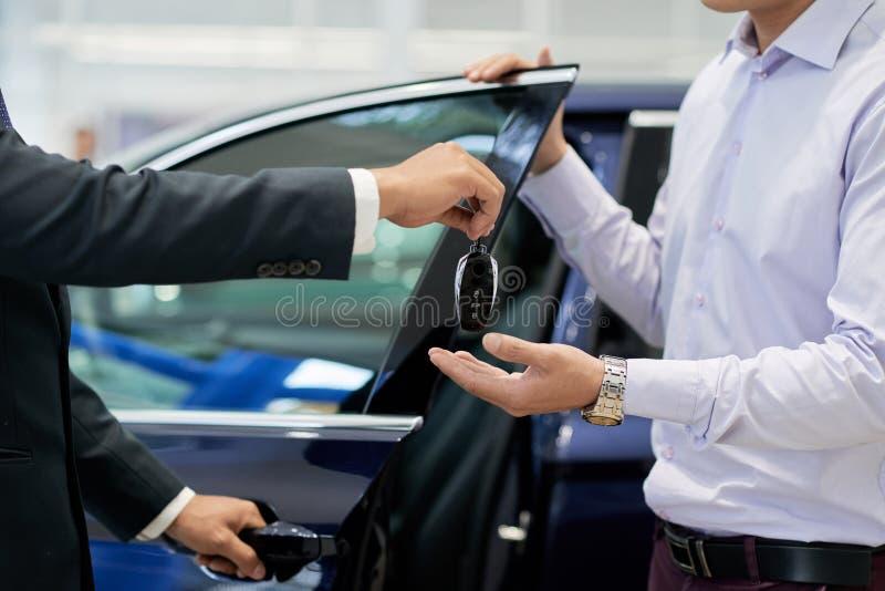 Verkoper die autosleutels geven royalty-vrije stock afbeeldingen