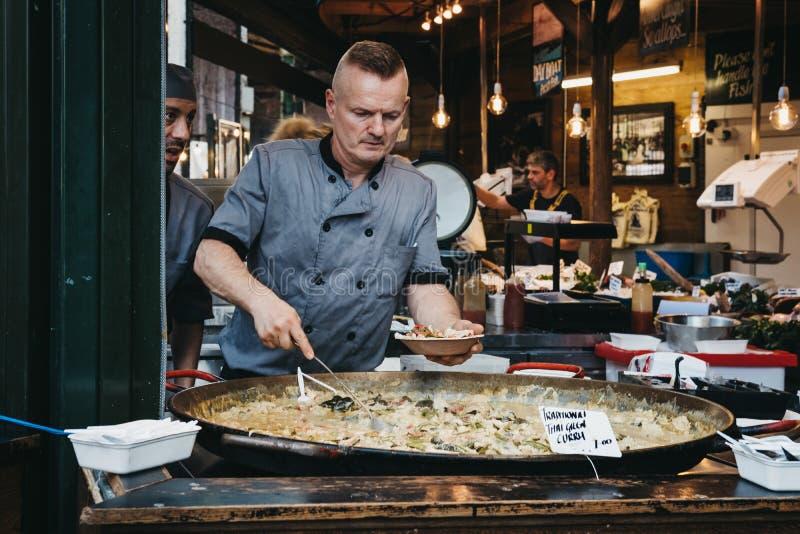 Verkoper die een gedeelte van Groene Thaise Kerrie in een kom zetten bij een stre stock foto