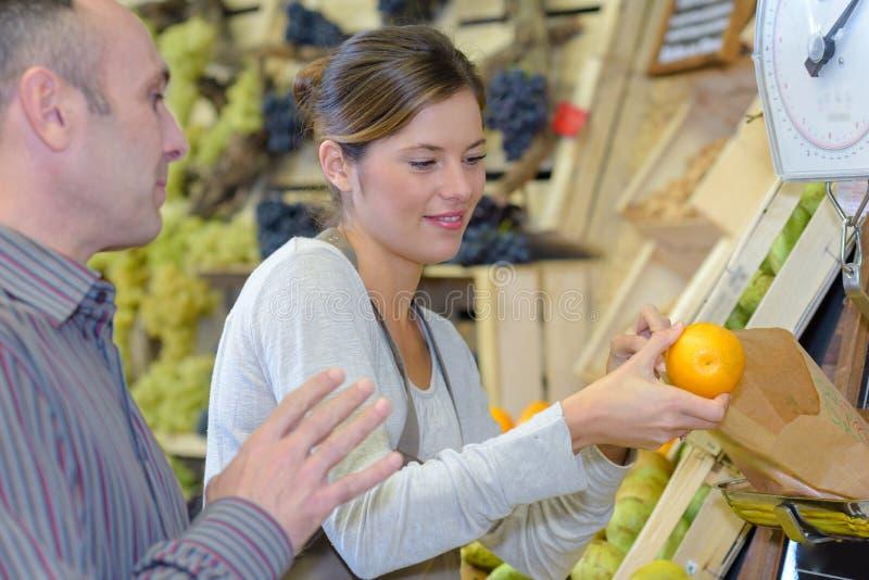 Verkoper die een sinaasappel wegen royalty-vrije stock foto's