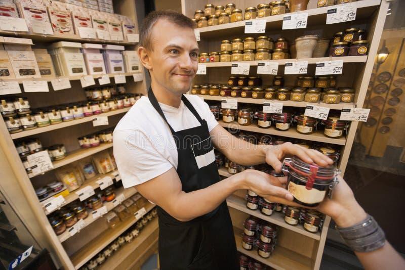Verkoper die kruik jam geven aan vrouwelijke klant in kruidenierswinkelopslag stock foto's