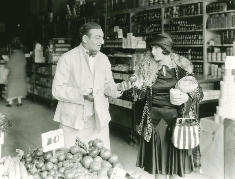 Verkoper die met vrouw bij markt onderhandelen stock foto