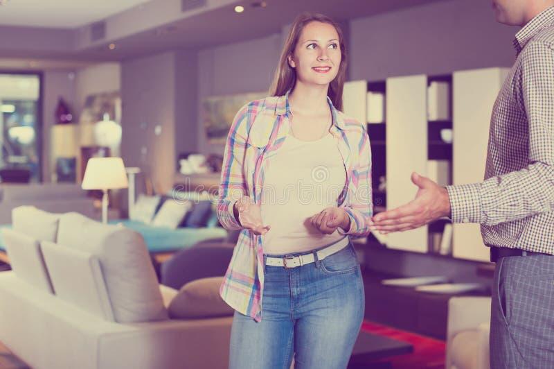 Verkoper die meubilairvarianten aanbieden aan positieve vrouw in salon stock foto's