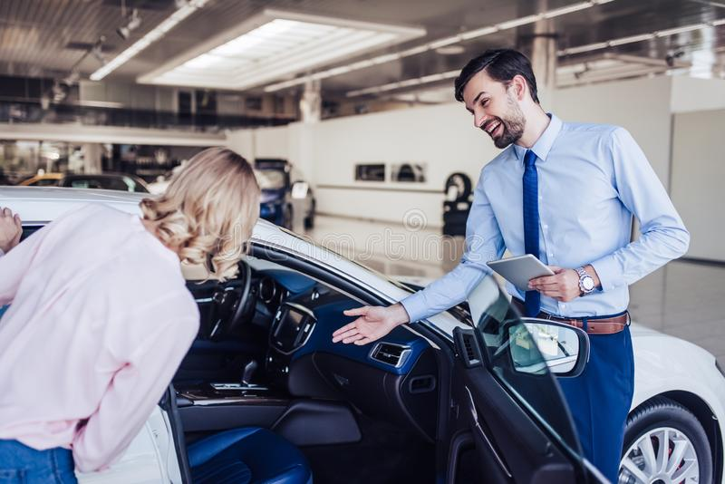 Verkoper die nieuwe auto met vrouw bekijken stock afbeeldingen