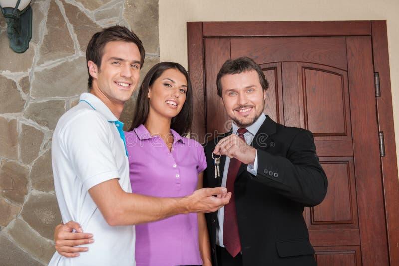 Verkoper die sleutels geven aan bezitseigenaars stock foto's