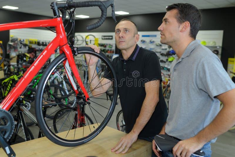 Verkoper in fietswinkel die aan cliënt verkopen royalty-vrije stock foto