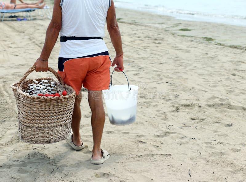 Verkoper op het strand met fruitvleespennen met verse vruchten worden gemaakt die stock afbeeldingen