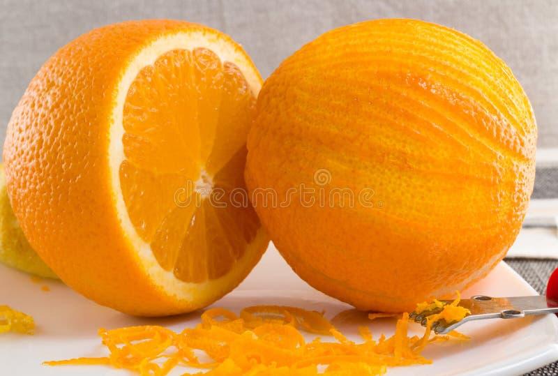Verkratztes Orange und dünn Locken der orange Schale auf weißer Platte lizenzfreie stockfotografie