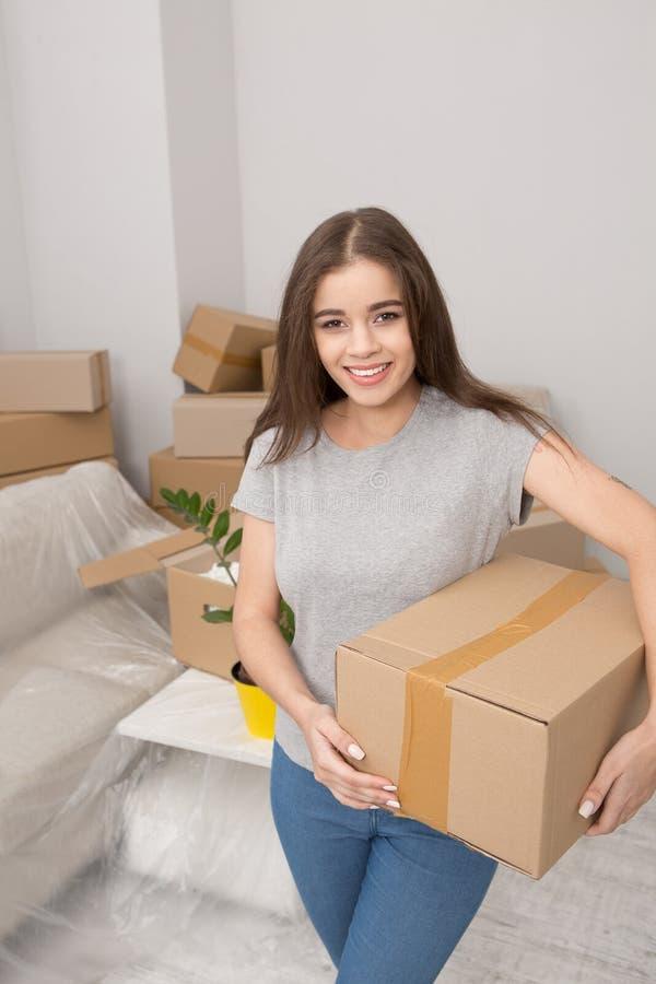Verlagern der jungen Frau, Kasten bereit halten, Sachen in eben gemieteter Wohnung auszupacken stockfotografie