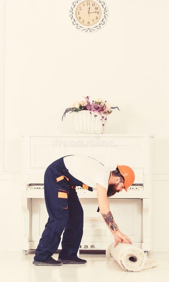 Verlagern des Konzeptes Lader wrappes Teppich in Rolle Kurier liefert Möbel im Falle sich bewegen heraus, Verlegung Mann lizenzfreies stockfoto