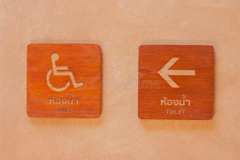 Verlam toilettekens op houten raad die met pijl manier op kleimuur richten stock fotografie