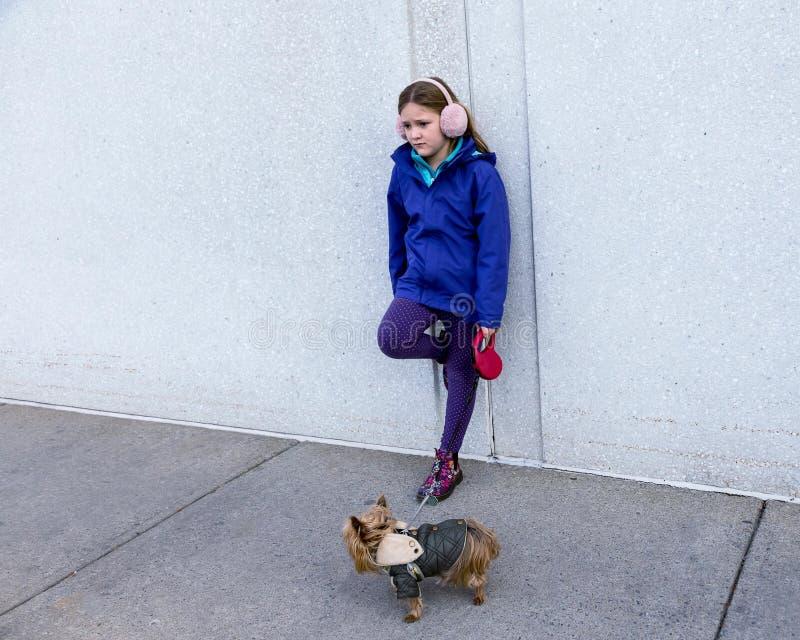 Verlassen-aussehendes kleines Mädchen, das auf Wand beim Halten kleinen Hundes Yorkshires Terrier auf Leine sich lehnt lizenzfreie stockfotos
