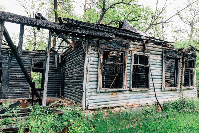 Verlassen nach altem Holzhaus des Feuers stockbild