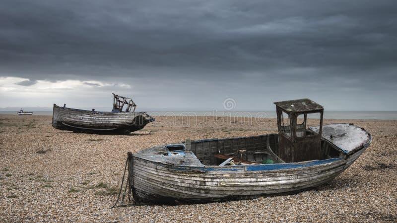 Verlassene Fischerboote auf Schindelstrand gestalten im Winter landschaftlich stockfoto