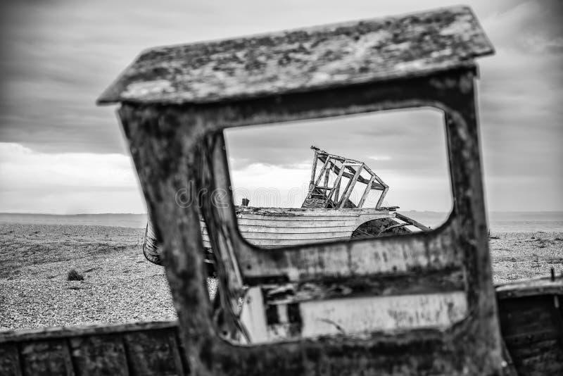 Verlassene Fischerboote auf Schindelstrand gestalten im Winter landschaftlich stockfotografie