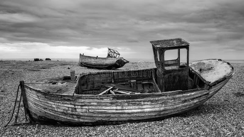 Verlassene Fischerboote auf Schindelstrand gestalten im Winter landschaftlich lizenzfreies stockbild