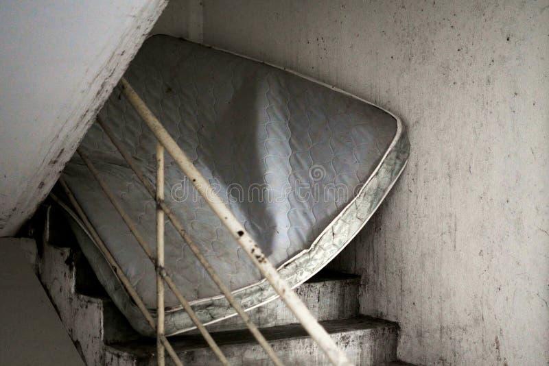 Verlassene schmutzige Matratze, die beflecktes Treppenhaus von unterhalb blockiert stockbild