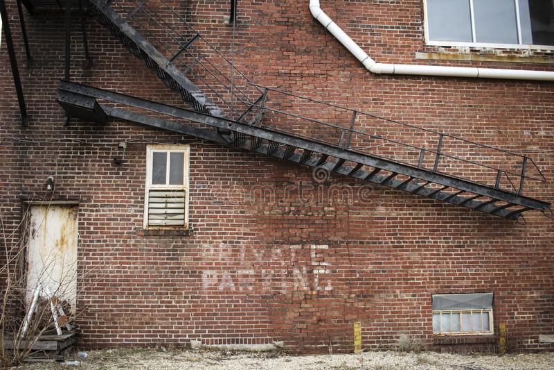 Verlassener Backsteinbau mit Metalltreppenhaus stockfotografie