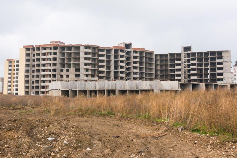 Verlassener Bau des Wohnkomplexes des multi Geschosses, überwältigt mit Unkräutern lizenzfreie stockfotografie