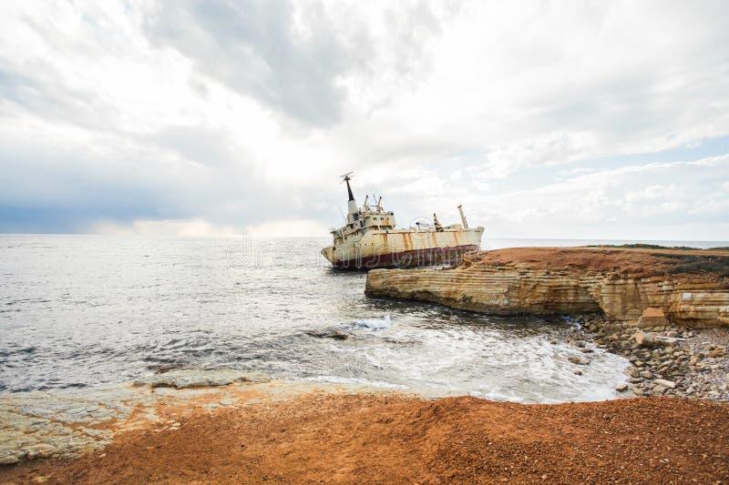 Verlassener gebrochener Schiffbruch setzte auf felsigem Seeufer auf den Strand lizenzfreie stockfotografie