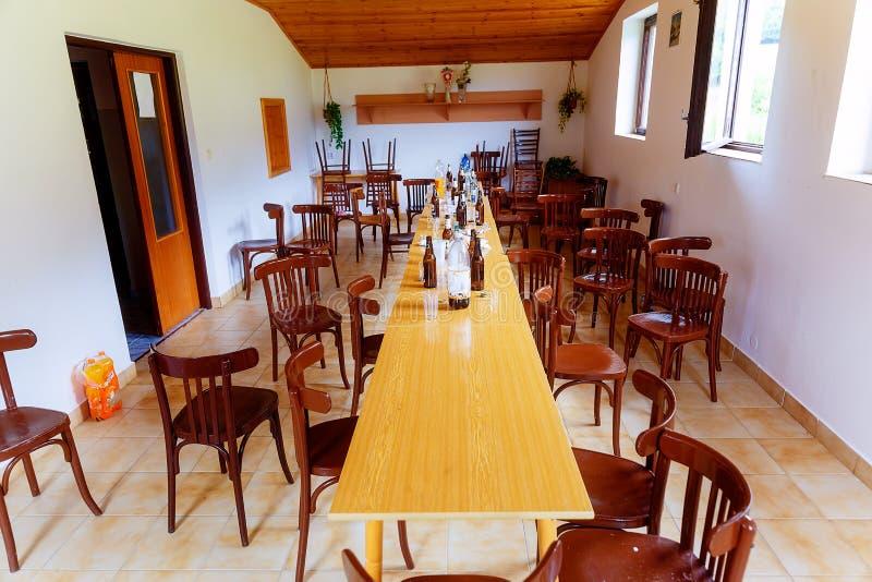 Verlassener Raum mit Stühlen, Tabellen und und leeren Flaschen nach der Partei, die vorbei ist lizenzfreie stockfotografie