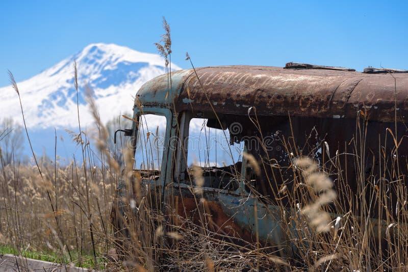 Verlassener und rostiger alter sowjetischer russischer Bus mitten in Schilfen und Landwirtschaftsfeldern mit Mt Ararat auf dem Hi stockfotografie
