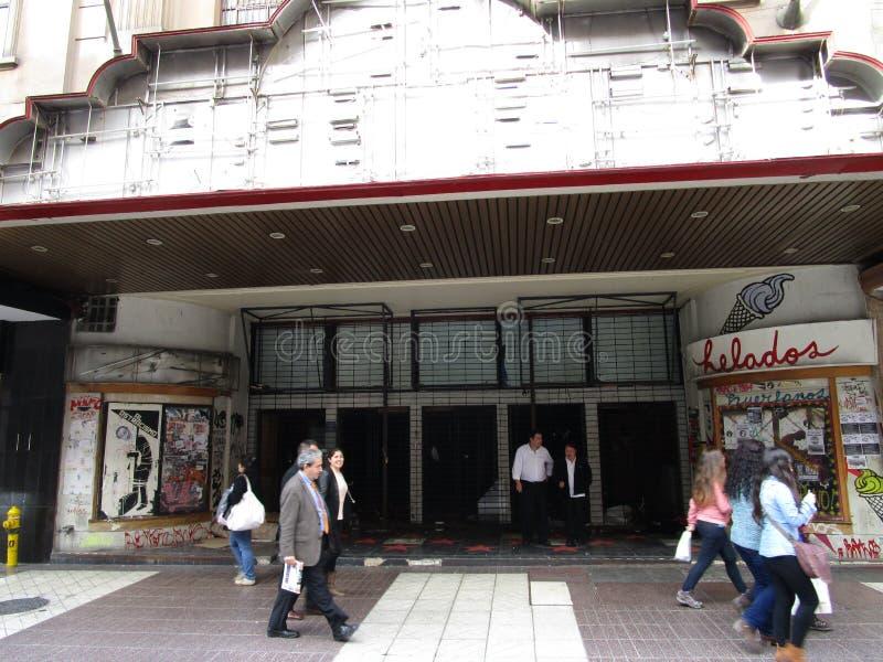 Verlassenes altes Kino mit den Leuten, die vorbei überschreiten lizenzfreie stockfotografie