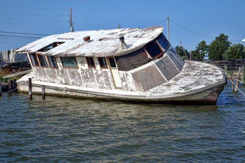 Verlassenes aufgegebenes Boot, das nach Hurrikan sinkt stockfoto