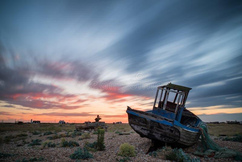 Verlassenes Fischerboot auf Strandlandschaft bei Sonnenuntergang lizenzfreie stockfotografie