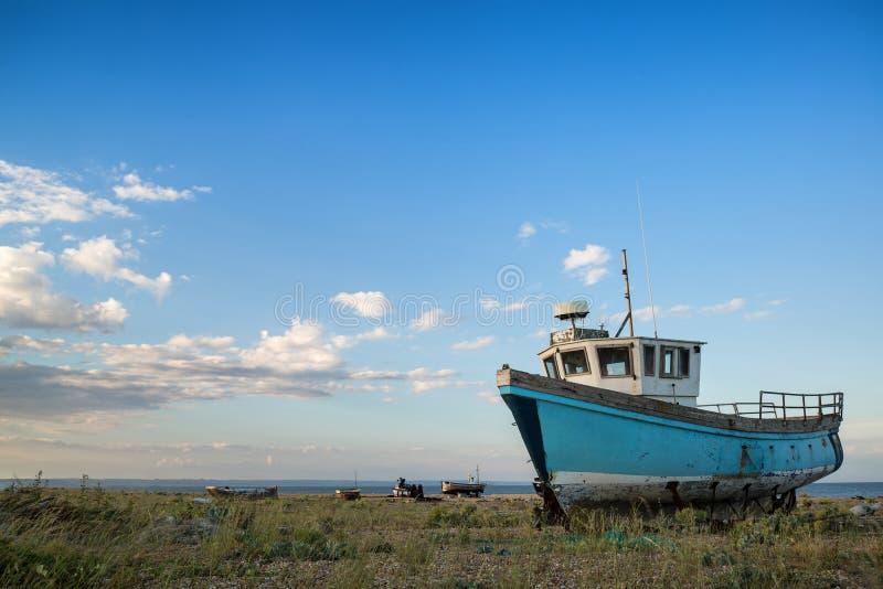 Verlassenes Fischerboot auf Strandlandschaft bei Sonnenuntergang lizenzfreies stockfoto