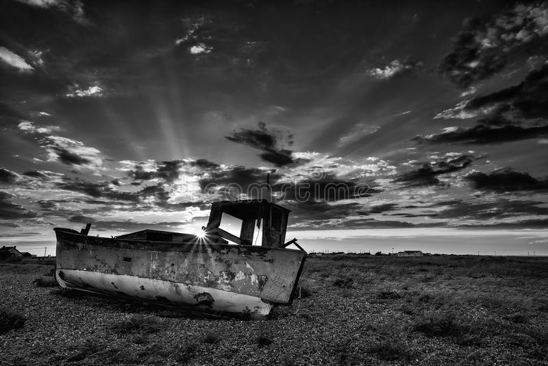 Verlassenes Fischerboot auf Strandschwarzweiss-Landschaft an der Sonne lizenzfreie stockbilder