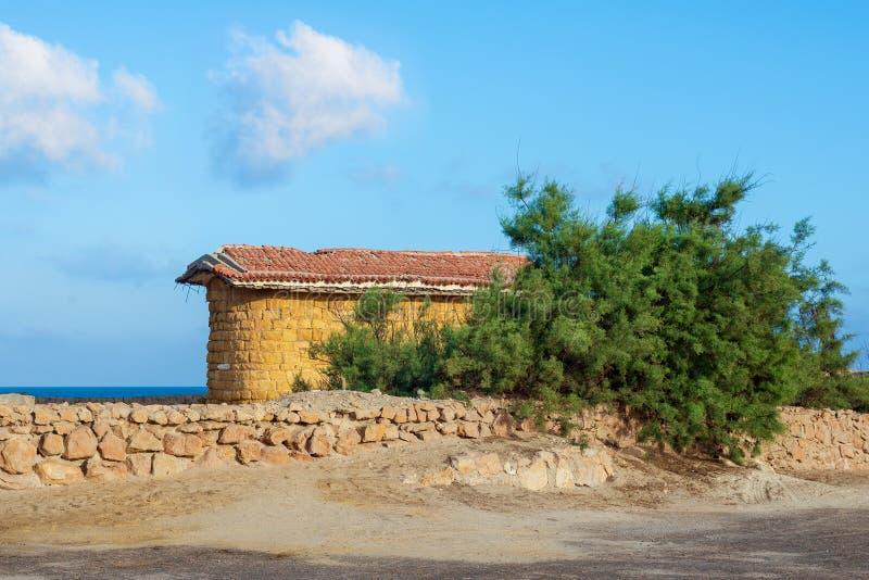 Verlassenes Gebäude von Steinziegelsteinen und von rotem mit Ziegeln gedecktem Dach, grüner Baum des Kurzschlusses und Steinzaun  lizenzfreie stockfotografie
