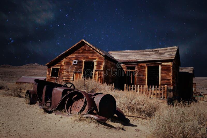 Verlassenes Holzhaus und rostiges Auto in der Wüste auf sternenklarer Nacht stockbild