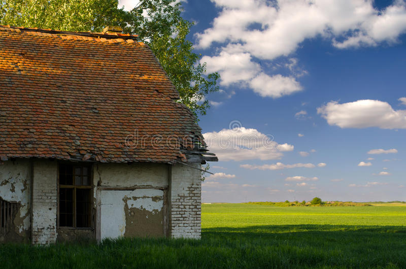 Verlassenes Landhaus und landwirtschaftliche Felder auf sonnigem Sommer stockfotografie