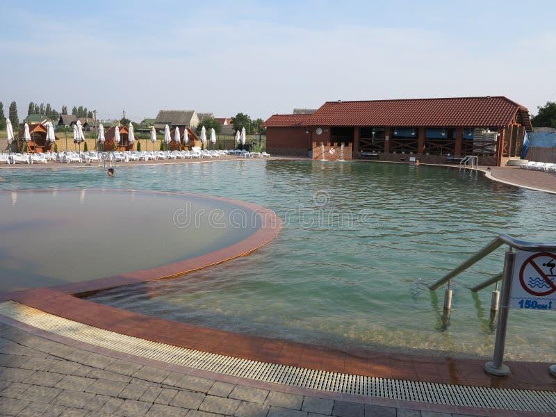 Verlassenes Pool mit klarem klarem Wasser und Stellung auf der gegenüberliegenden Seite der Sonnenruhesessel und der gefalteten R stockfoto
