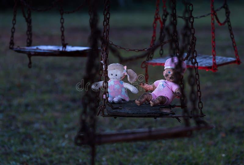 Verlaten childs pop en zacht stuk speelgoed op schommeling stock foto's