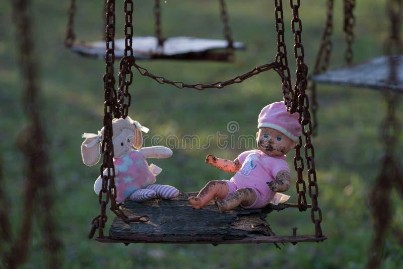 Verlaten childs pop en zacht stuk speelgoed op schommeling stock afbeeldingen