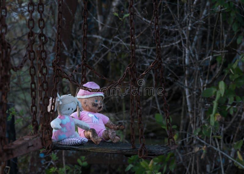 Verlaten childs pop en zacht stuk speelgoed op schommeling royalty-vrije stock foto