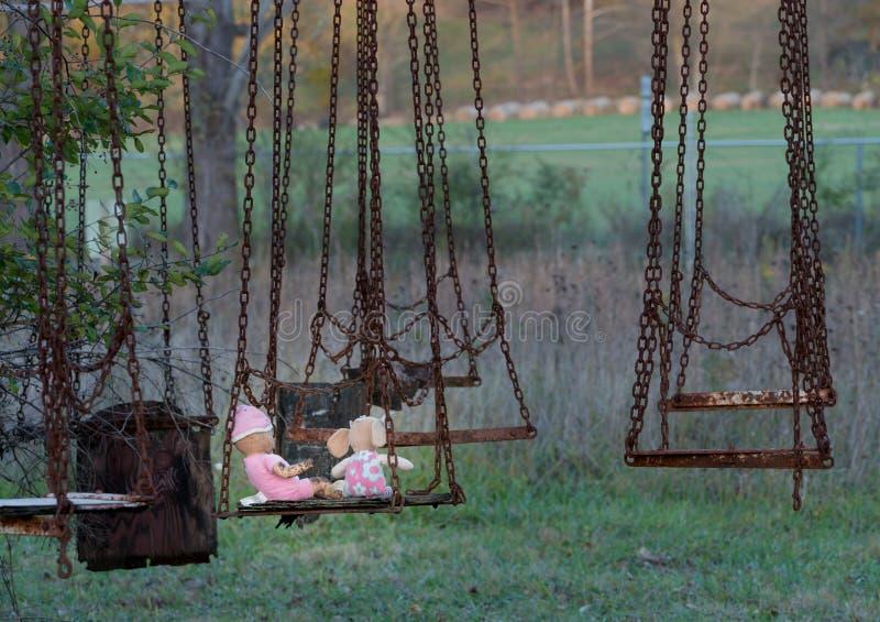 Verlaten childs pop en zacht stuk speelgoed op schommeling royalty-vrije stock fotografie