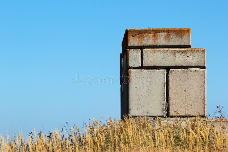 Verlaten concrete blokken van de onvolledige bouw tegen blauwe hemel stock foto's
