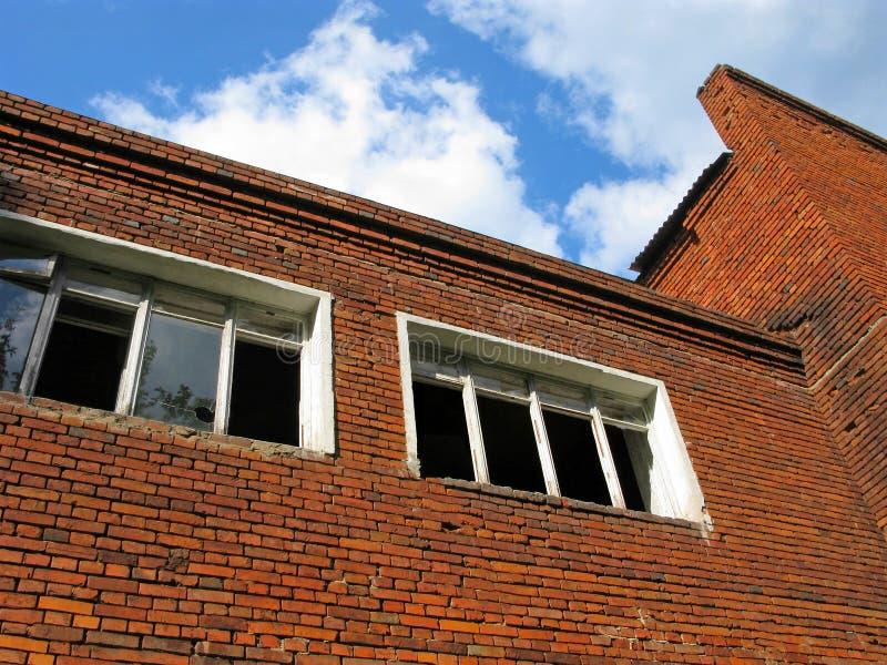 Verlaten de baksteenbouw, gebroken en lege vensters stock foto