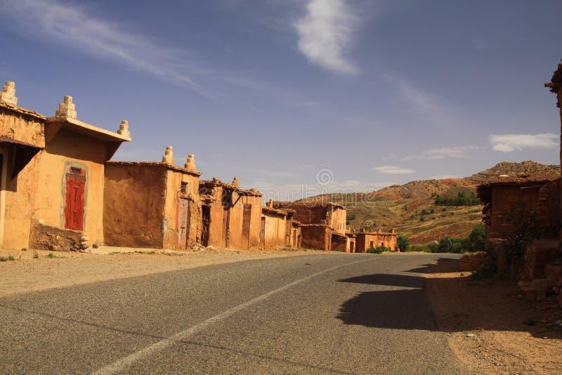 Verlaten dorp van kleihuizen langs lege weg in Atlasbergen, Marokko stock fotografie