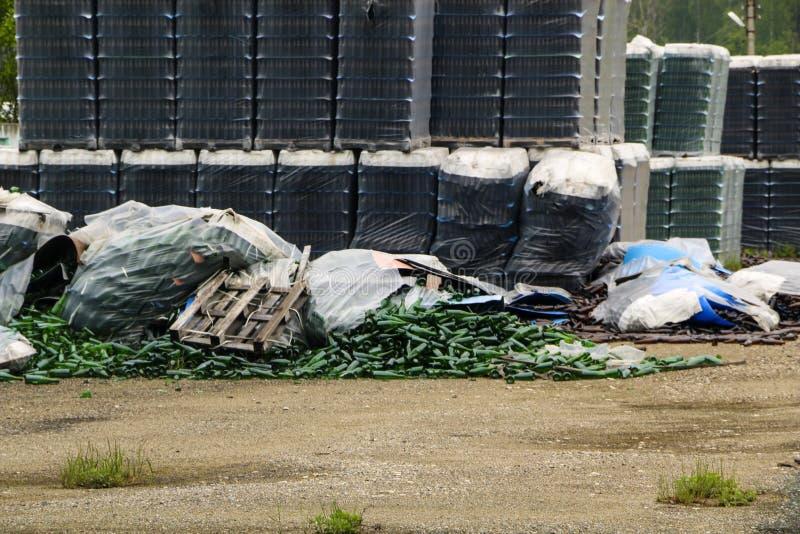 Verlaten glasfabriek ingepakte flessen in pallets, gebroken flessen op asfalt, veel losse flessen en huisvuil van productie stock foto's