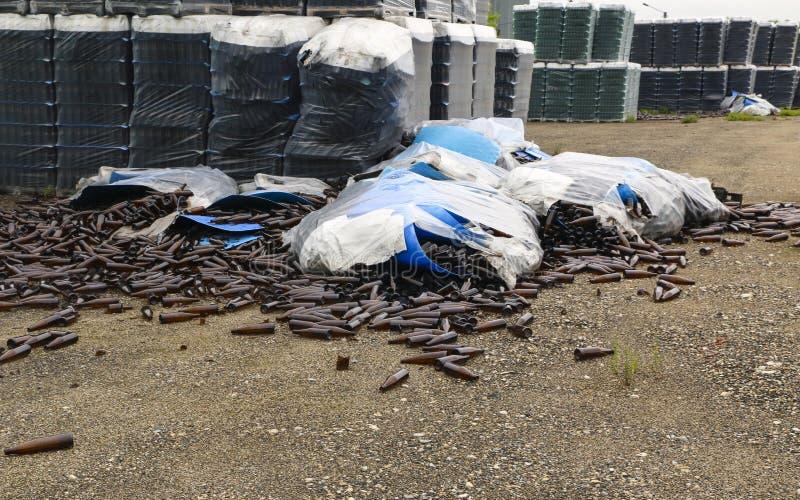 Verlaten glasfabriek ingepakte flessen in pallets, gebroken flessen op asfalt, veel losse flessen en huisvuil van productie stock foto