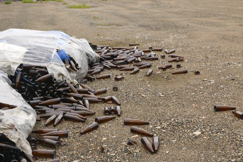 Verlaten glasfabriek ingepakte flessen in pallets, gebroken flessen op asfalt, veel losse flessen en huisvuil van productie royalty-vrije stock foto