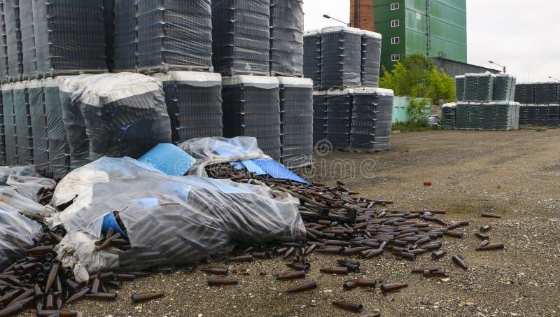 Verlaten glasfabriek ingepakte flessen in pallets, gebroken flessen op asfalt, veel losse flessen en huisvuil van productie stock afbeeldingen