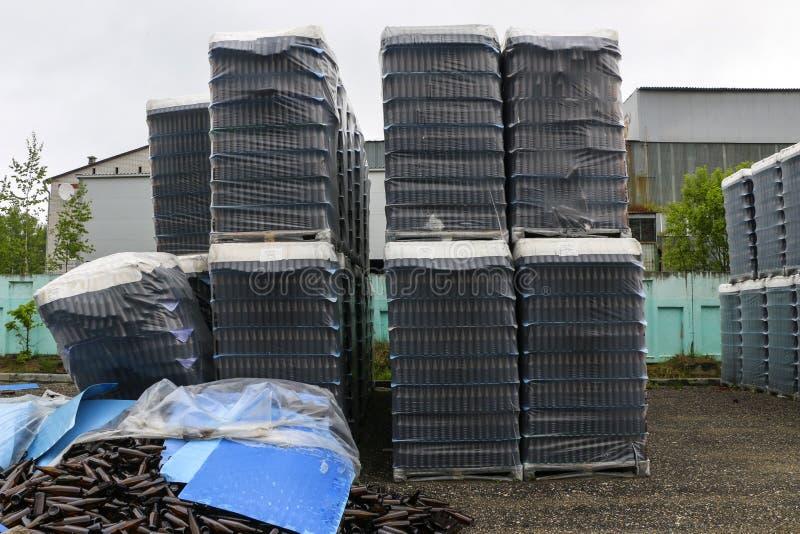 Verlaten glasfabriek ingepakte flessen in pallets, gebroken flessen op asfalt, veel losse flessen en huisvuil van productie royalty-vrije stock foto's