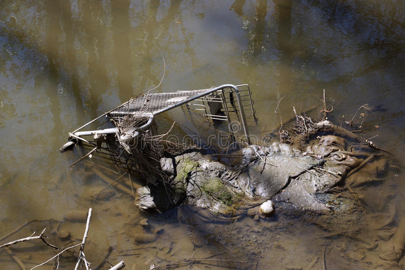 Verlaten het winkelen karretje in modderig water stock fotografie