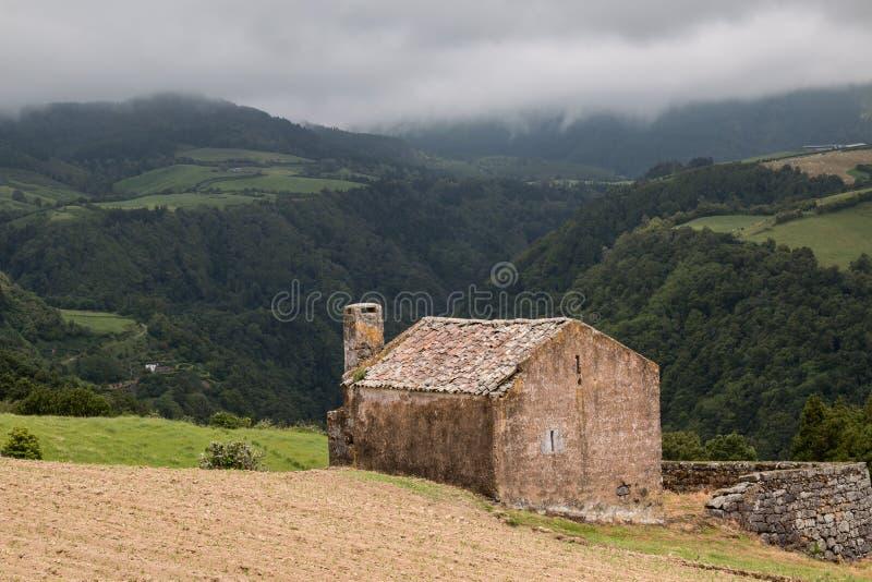 Verlaten huis in een bergenvallei stock foto's