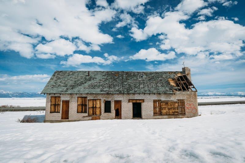 Verlaten huis met graffiti in de sneeuw stock foto's