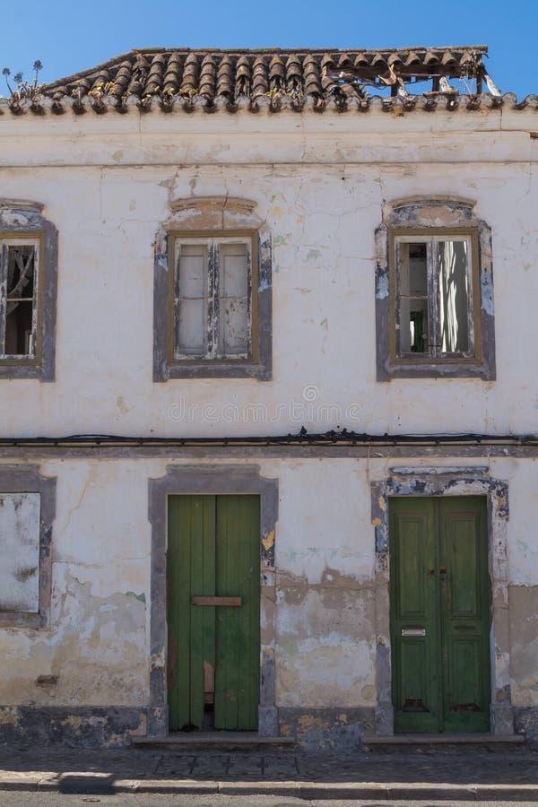 Verlaten huis met groene deuren stock afbeelding
